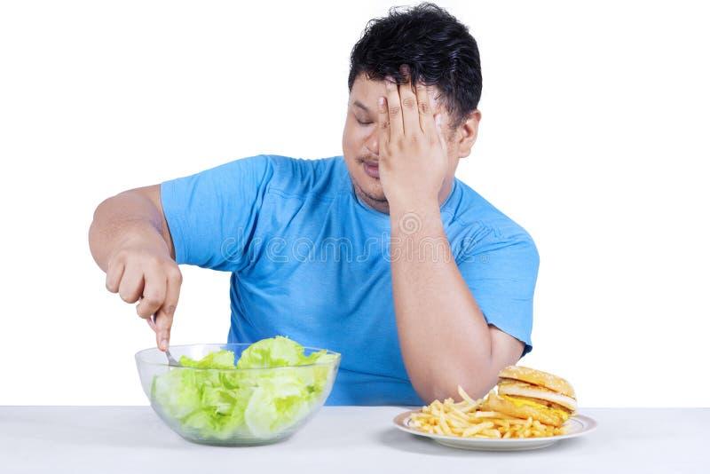 La persona gorda elige comer la ensalada imagen de archivo libre de regalías