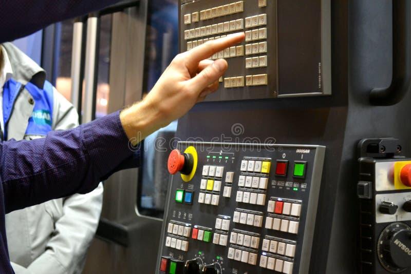 La persona lavora dietro il pannello di controllo della macchina di produzione fotografia stock
