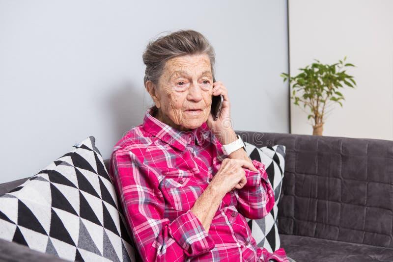 La persona mayor del tema utiliza tecnología Hogar que se sienta de la alegría de la sonrisa del pelo de la mujer caucásica gris  imagenes de archivo