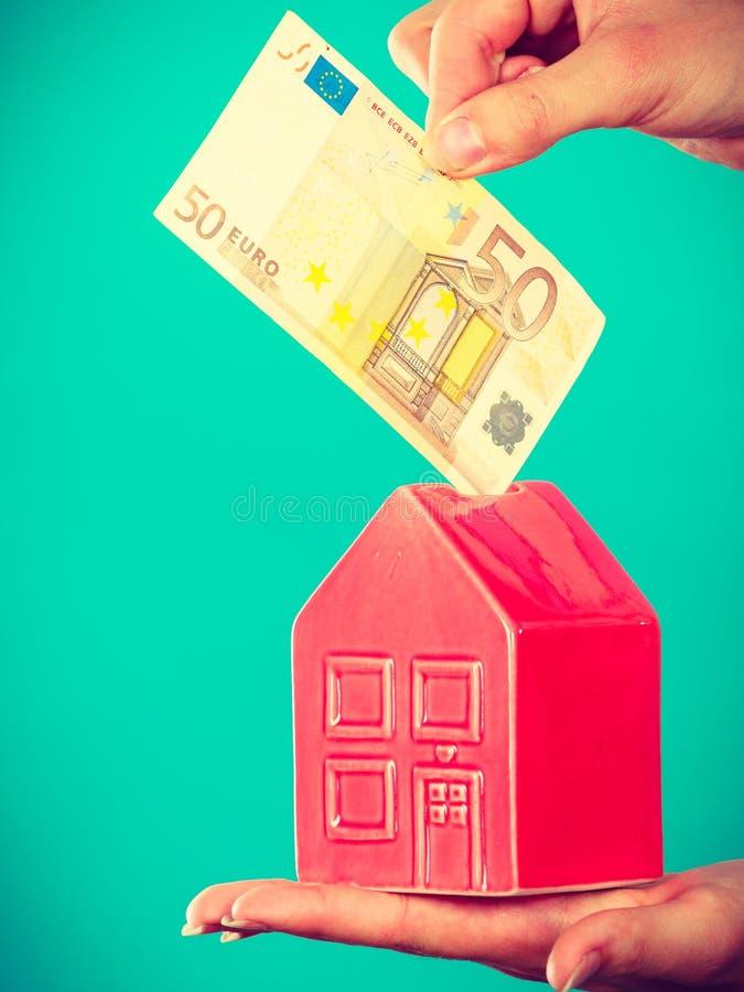 La persona pone el dinero en piggybank de la casa imagenes de archivo