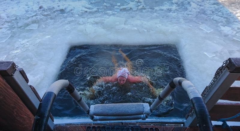 La persona que emergía de un agujero de natación cortó en hielo fotografía de archivo libre de regalías