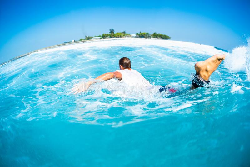 La persona que practica surf bate y saca la ola oceánica tropical foto de archivo