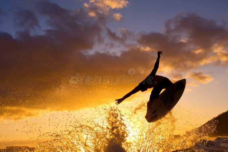 La persona que practica surf consigue el aire grande en la puesta del sol imágenes de archivo libres de regalías