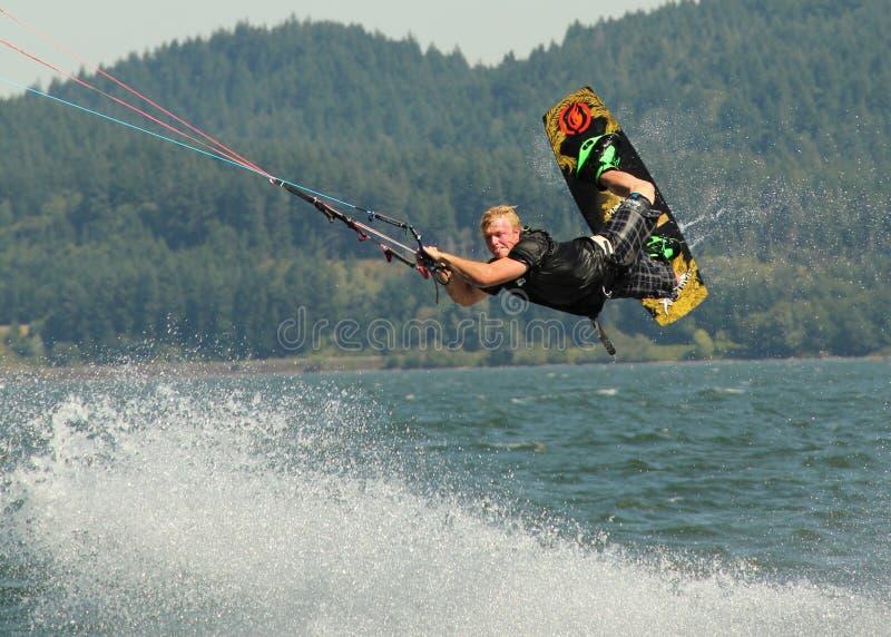 La persona que practica surf de la cometa realiza detrás el rasguño foto de archivo