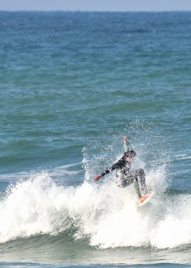 La persona que practica surf de la onda monta dentro de un chapoteo fotografía de archivo libre de regalías