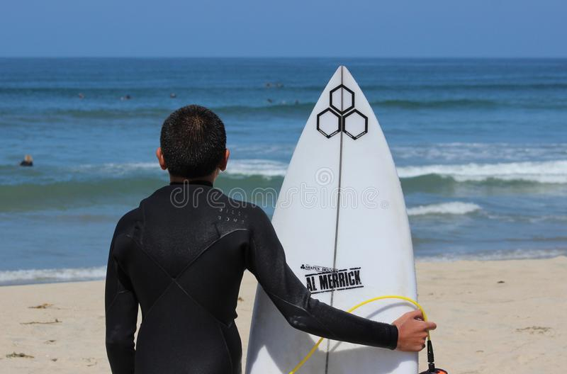 La persona que practica surf del muchacho mira ondas fotos de archivo