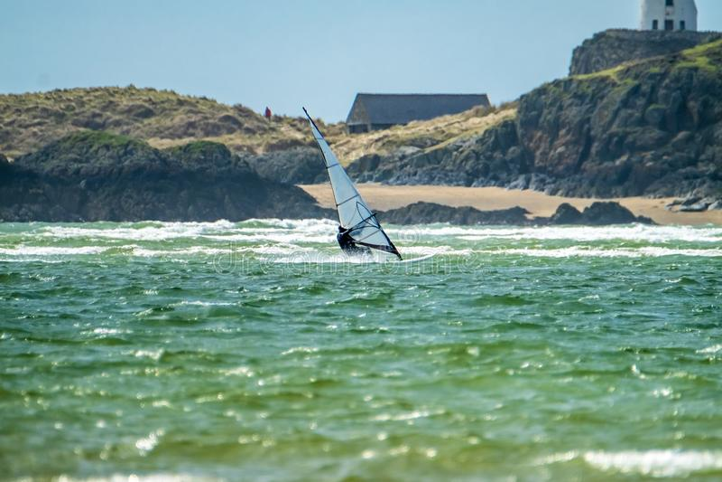 La persona que practica surf del viento goza de la playa en Newborough Warren con la isla de Llanddwyn en el fondo, isla de Angle foto de archivo