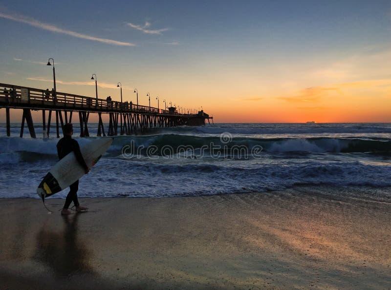 La persona que practica surf en la playa imperial en San Diego, California se encendió por una puesta del sol imponente fotos de archivo