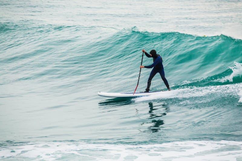 La persona que practica surf encendido se levanta el tablero de paleta en onda azul El invierno se levanta la paleta que practica imagenes de archivo