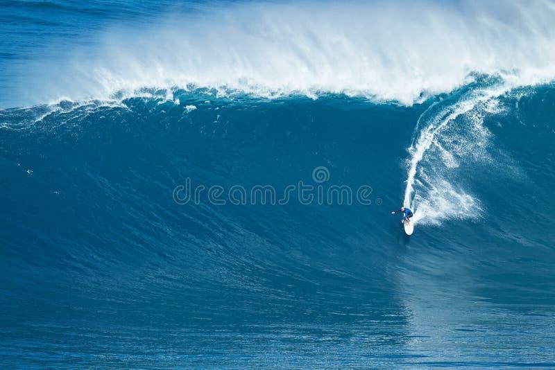 La persona que practica surf monta la onda gigante en los mandíbulas fotos de archivo