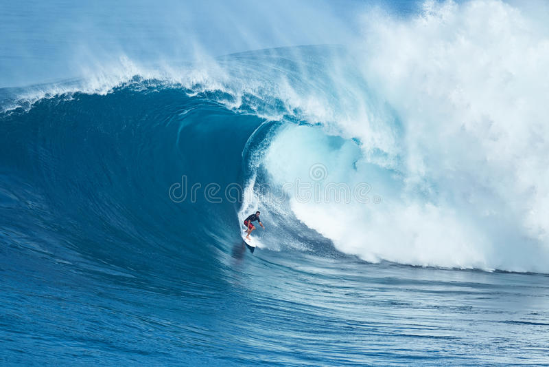 La persona que practica surf monta la onda gigante en los mandíbulas imagenes de archivo