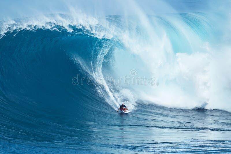 La persona que practica surf monta la onda gigante en los mandíbulas fotografía de archivo libre de regalías