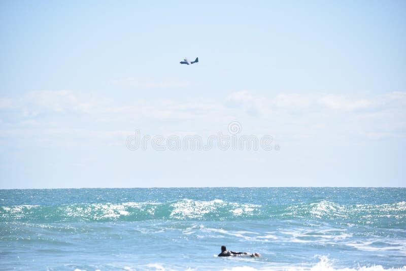 La persona que practica surf se bate hacia fuera mientras que el aeroplano vuela sobre horizonte imágenes de archivo libres de regalías