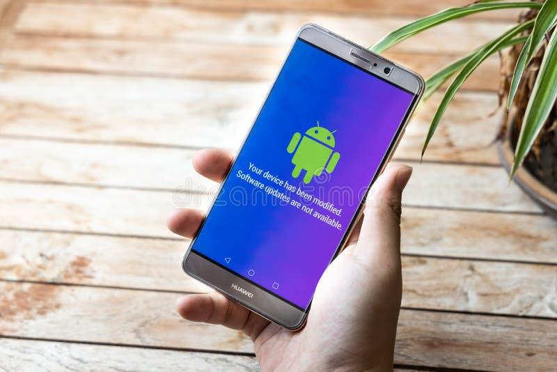 La persona que sostiene el tel?fono del compa?ero de Huawei con las actualizaciones de software del mensaje de Android no est? di fotografía de archivo libre de regalías