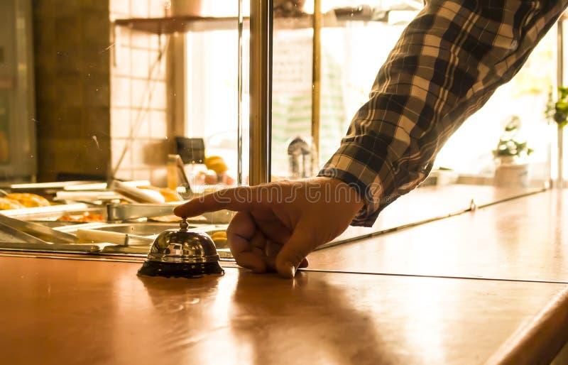 La persona suena la campana en el contador en el café foto de archivo