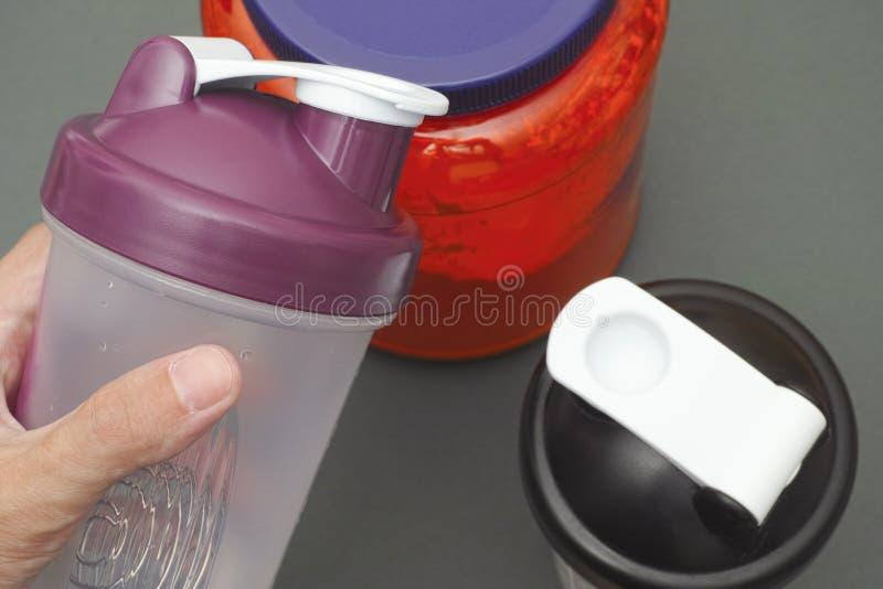 La persona tiene l'agitatore vuoto in sua mano sopra il barattolo della proteina immagine stock