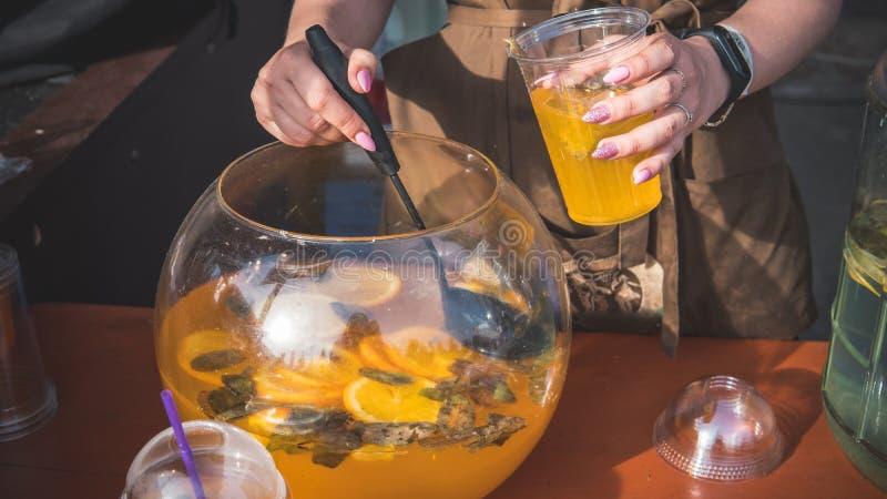 La persona versa la limonata in un vetro Alimento e bevande della via Cocktail della frutta fresca in un vetro di plastica immagine stock
