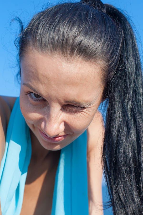 La personne d'une chevelure foncée avec la queue de cheval regarde l'appareil-photo et cligne de l'oeil photos stock