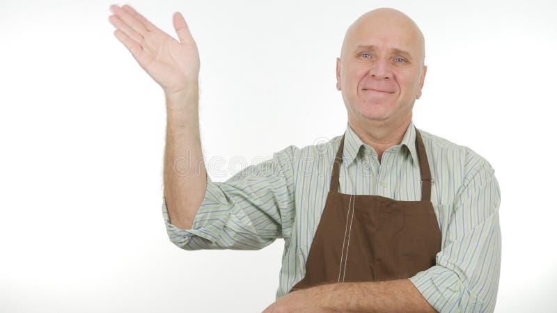 La personne de sourire avec le tablier font bonjour à signe des gestes de main de salut photos stock
