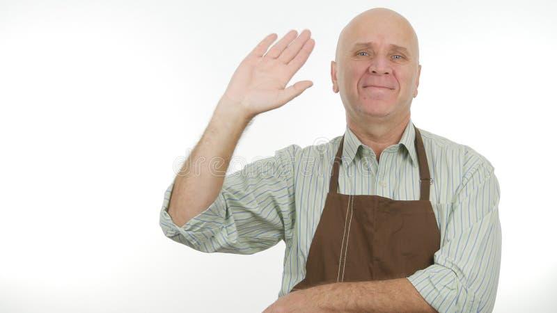 La personne de sourire avec le tablier font bonjour à signe des gestes de main de salut photo stock