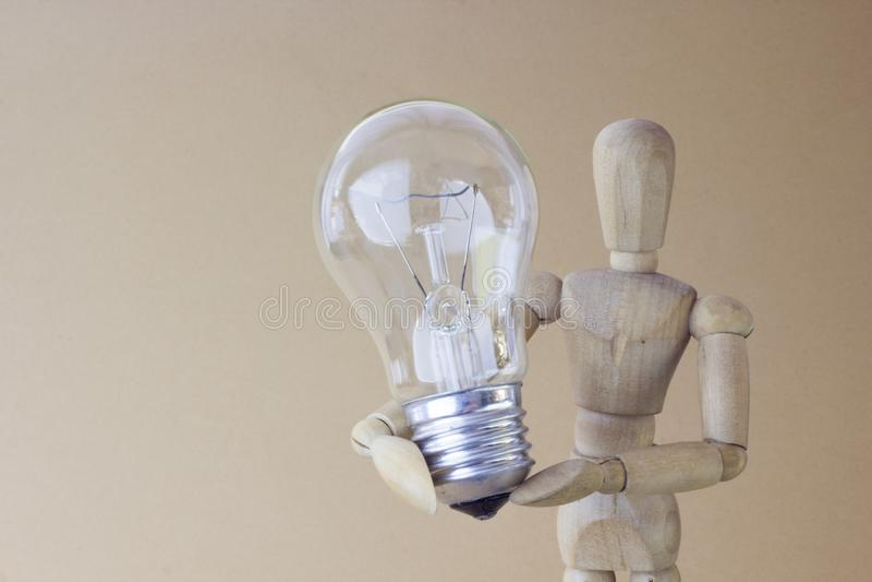 La personne en bois juge l'ampoule électrique disponible photos libres de droits