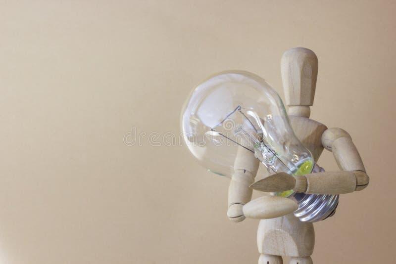 La personne en bois juge l'ampoule électrique disponible image stock