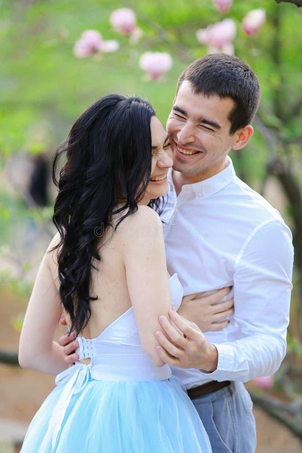 La personne féminine et la brune de sourire de jeunes équipent étreindre près de l'arbre de floraison images libres de droits