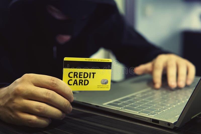 La personne inconnue emploie l'ordinateur et la carte de crédit pour commettre le crime de cyber Le transgresseur d'ordinateur em photographie stock