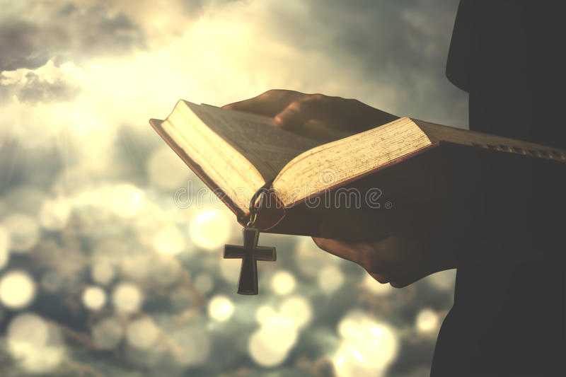 La personne lit la bible avec le chapelet image stock