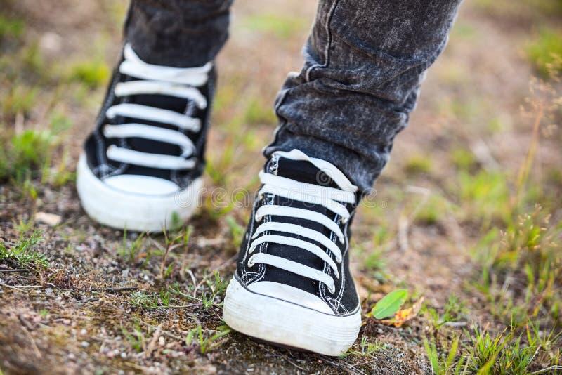 La personne méconnaissable dans des chaussures en caoutchouc marche sur le sentier piéton, vue de face photo libre de droits