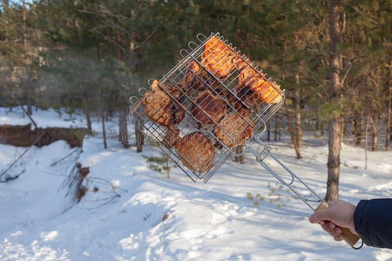 La personne qui grille le porc ou le boeuf sur le gril ou le gril homme tenant un gril avec de la viande photos libres de droits