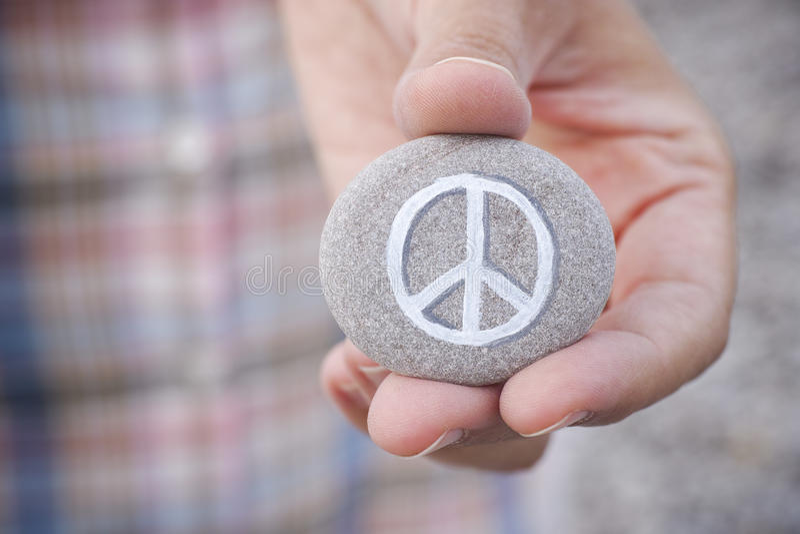La personne tient la pierre avec le symbole de paix image libre de droits