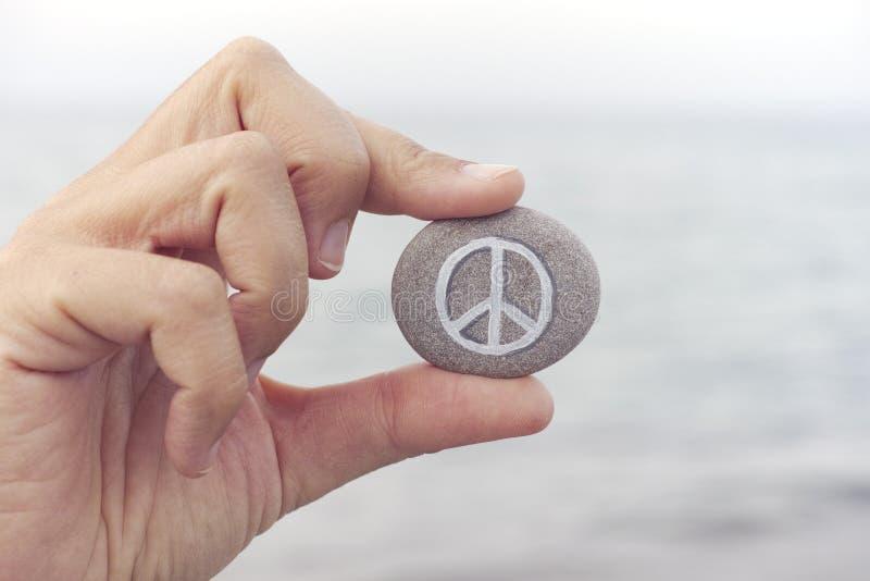 La personne tient la pierre avec le symbole de paix contre la mer à l'arrière-plan image stock