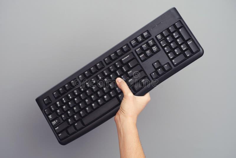 La personne tient le clavier sans fil noir dans sa main image libre de droits