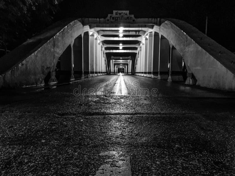 La perspective étonnante et le point de disparaition avec le vieux pont blanc la nuit, asphaltent la couche de surface humide images libres de droits