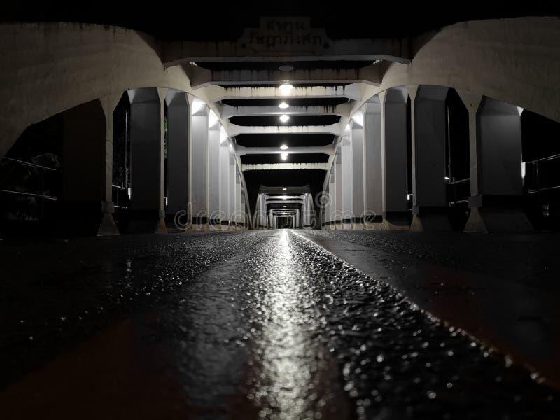 La perspective étonnante et le point de disparaition avec le vieux pont blanc la nuit, asphaltent la couche de surface humide images stock