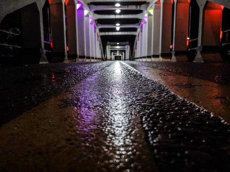 La perspective étonnante et le point de disparaition avec le vieux pont blanc la nuit, asphaltent la couche de surface humide photos stock