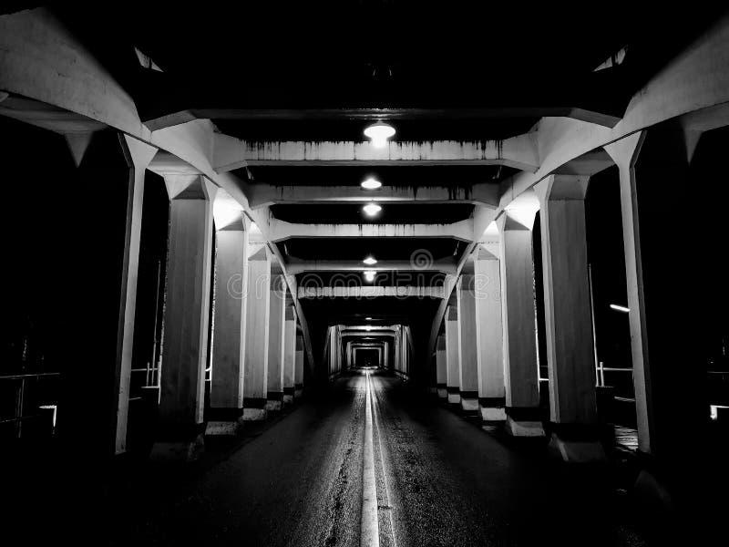La perspective étonnante et le point de disparaition avec le vieux pont blanc la nuit, asphaltent la couche de surface humide photographie stock