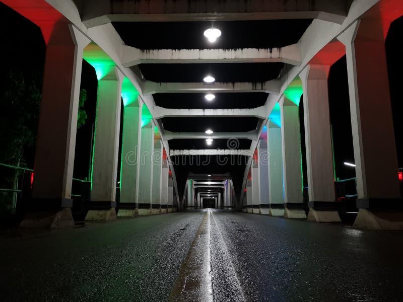 La perspective étonnante et le point de disparaition avec le vieux pont blanc la nuit, asphaltent la couche de surface humide photos libres de droits
