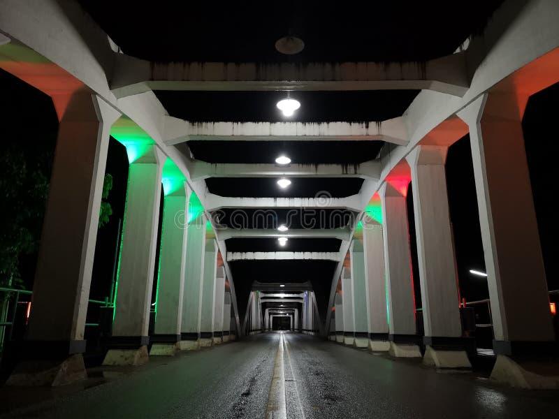 La perspective étonnante et le point de disparaition avec le vieux pont blanc la nuit, asphaltent la couche de surface humide image libre de droits