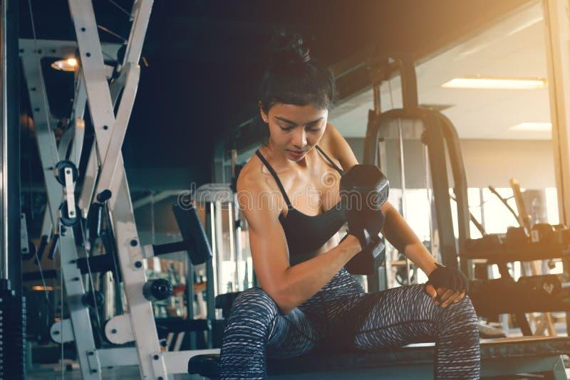 La pesa de gimnasia asiática de la tenencia de brazo del ` s de la mujer y levanta con el ABS fuerte a imagen de archivo libre de regalías