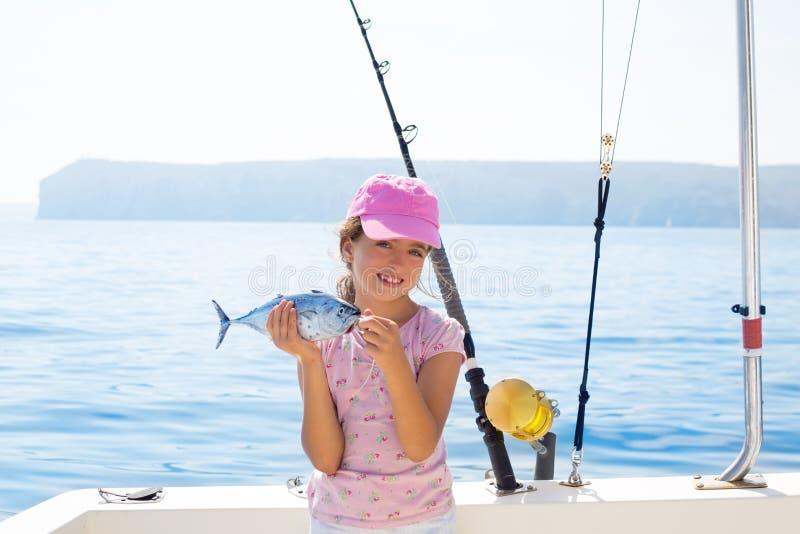 La pesca de la niña del niño en el barco que sostiene pequeños atunes pesca el catc foto de archivo
