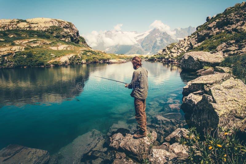 La pesca del giovane sul lago con le montagne della barretta abbellisce su fondo fotografia stock