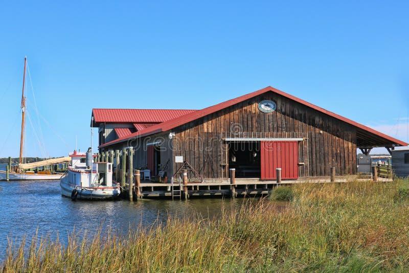 La pesca di Brown ha sparso con un tetto rosso, su un bacino vicino ad un piccolo porto fotografia stock