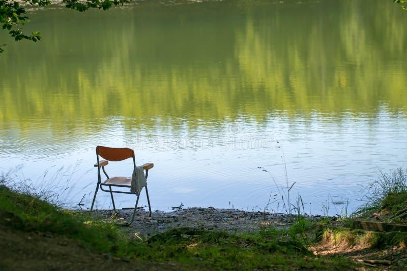 La pesca ida, quizás, preside a la izquierda por el borde del lago Verano Fondo, nadie allí en asiento de la orilla del lago imágenes de archivo libres de regalías