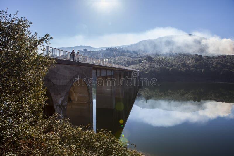 La Pesga bridge over Gabriel y Galan Reservoir waters, Spain. La Pesga bridge over Gabriel y Galan Reservoir waters, Caceres, Spain. Local people crossing the stock photography