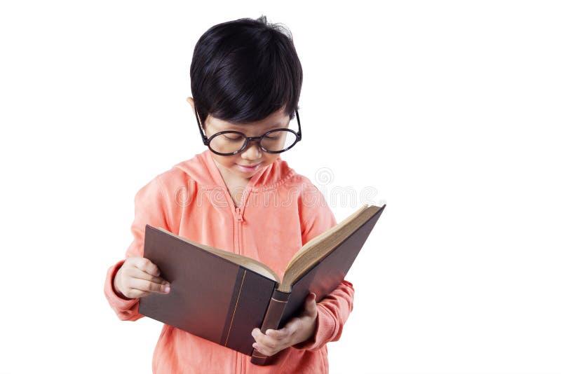 La petite écolière lit le livre dans le studio image libre de droits