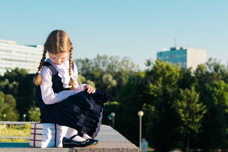 La petite écolière s'assied sur un manuel pour l'école images libres de droits