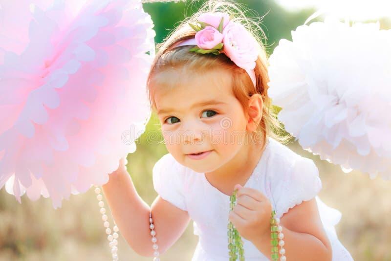 La petite belle fille dans la robe de fête est légère entre deux pompons de papier énormes photographie stock