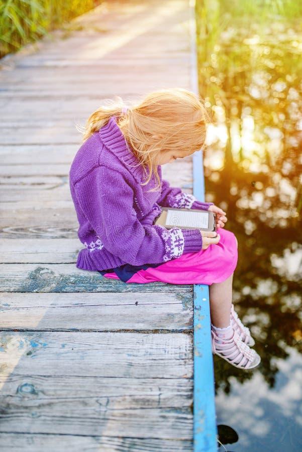 La petite belle fille a lu des e-livres photos stock